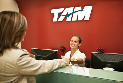 Staff member gives customer boarding pass at TAM desk